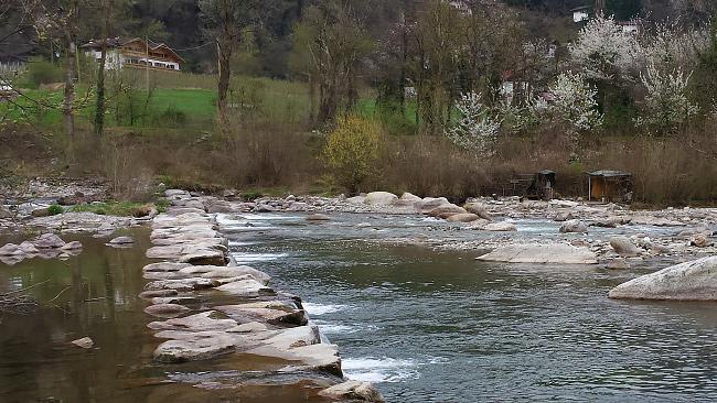 Una delle tante cascatelle artificiali le cui rocce sono utilizzate dai meranesi per guadare il fiume. Sull'altra sponda, sulla destra, si notano due ripari realizzati con rami e teloni